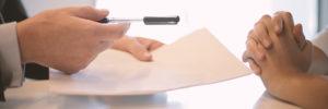 Vertrag und Stift werden an weitere Person ausgehändigt