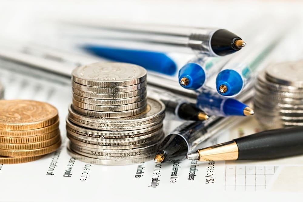 Einige Münzen sowie Kugelschreiber liegen auf Formularen