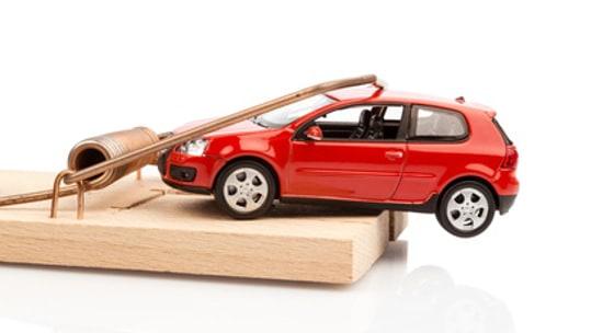 Ein Modellauto in einer Mausefalle, Symbolfoto für Autokosten und Schulden