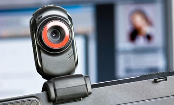 Webcam auf Monitor, im Hintergrund ein Screen mit Portrait einer Frau