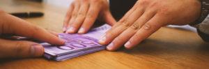 Man schiebt einen Stapel Euro-Geldscheine über den Tisch