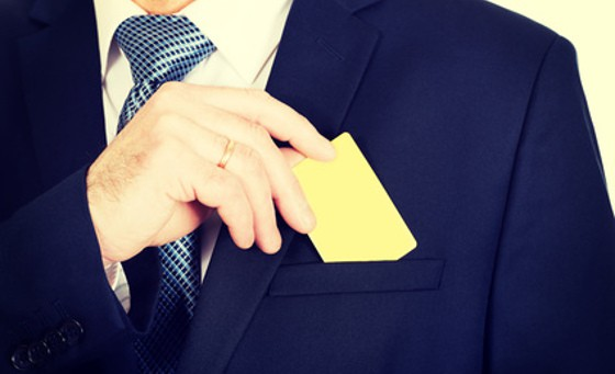 Mature businessman taking a yellow card from pocket.