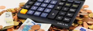 Taschenrechner liegt auf Geldmünzen und Geldscheinen