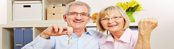 Erfolgreiches Paar Senioren jubelt zufrieden mit Haus und Schlüssel