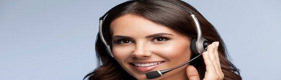 Portrait of cheerful customer support female phone operator in headset, against grey background. Consulting and assistance service call center.