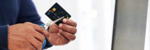 Person zerschneidet Kreditkarte