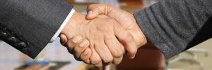 Handschlag zweier Männer im Anzug in einem Saal - Treuhandkonto eröffnen