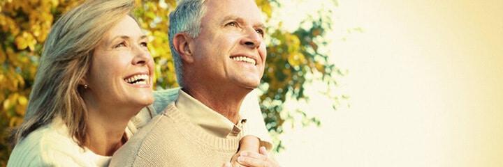 Älteres Ehepaar blickt zusammen Richtung Sonne - kredit voraussetzungen