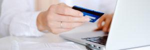Frau sitz am Laptop und hält Kreditkarte in der Hand
