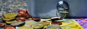 Euro-Münzen und Euro-Geldscheine liegen unter einem Geldkoffer