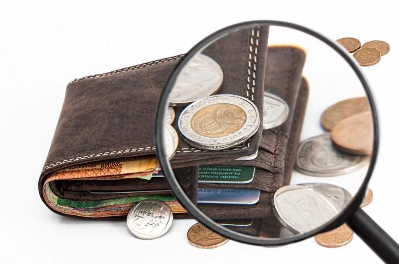 Geldbeutel mit Geldstücken, der durch eine Lupe betrachtet wird.