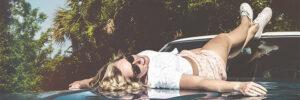 Frau liegt auf Motorhaube eines Auto